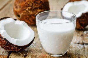 Glaasje kokos naast opengebroken kokosnoot