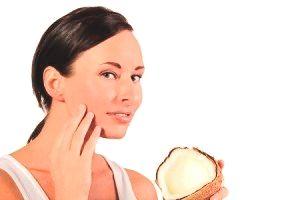 vrouw smeert kokosolie uit over haar gezicht
