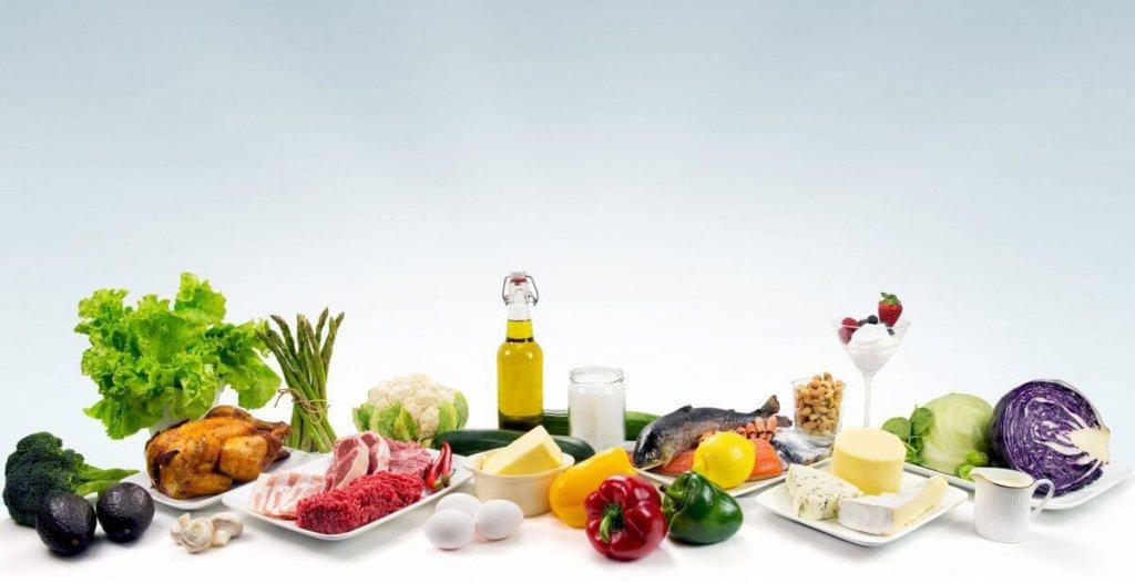 koolhydraatarme voedingsmiddelen op tafel met witte achtergrond