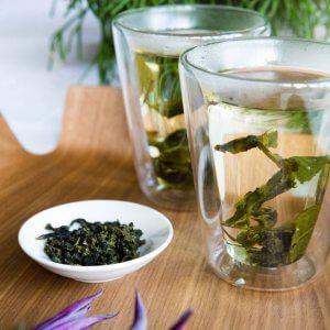 oolong thee bladeren in kommetje naast 2 thee glazen