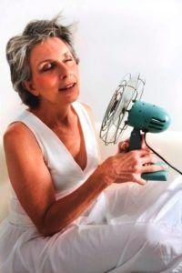 Oudere vrouw zoekt verkoeling bij ventilator