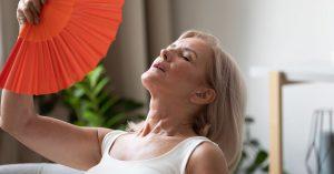 Femme utilisant un éventail pour apaiser les bouffées de chaleur de la préménopause