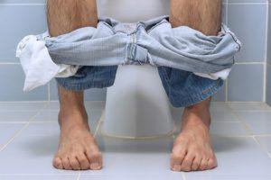 man zit verkrampt op het toilet