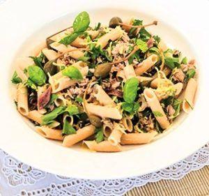 Penne pasta en olijven op wit bord