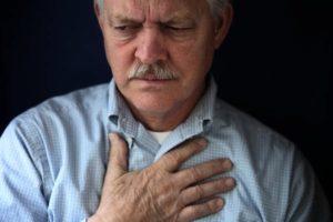 bezorgde oude man grijpt met zijn hand naar de borstkas