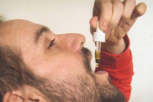 Man druppelt CBD olie op zijn tong