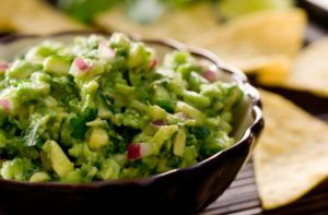 guacamole salade met salsa in een zwart kommetje uitbelicht