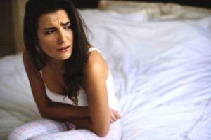 Vrouw zit op de rand van haar bed en heeft last van buikpijn