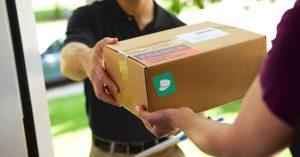 bezorger geeft pakketje af aan de deur