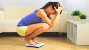 vrouw staat gehurkt op weegschaal en is gefrustreerd