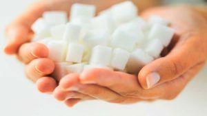 Vrouw houdt handjevol suikerklontjes vast