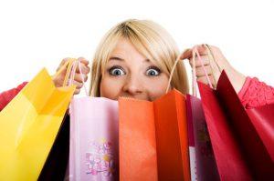 vrouw heft verschillende winkeltassen omhoog en trekt blij gezicht