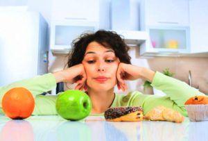 vrouw kijkt naar fruitstukken in de keuken