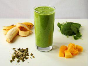 groene smoothie op tafel met verschillende soorten groenten ernaast