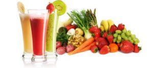 3 smoothie glazen en diverse fruit- en groentesoorten op achtergrond