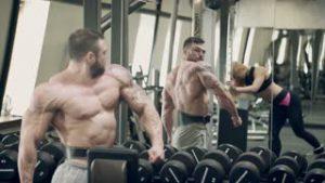 gespierde man kijkt in de spiegel naar zijn spieren