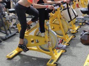 sporters doen aan spinning op gele fietstrainer