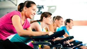 groep sportende vrouwen op fietstrainer volgen een spinning les