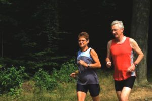 Oudere man en vrouw joggen door de bossen op klaarlichte dag