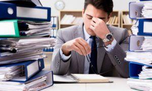 man op kantoor ervaart veel werkdruk en stress