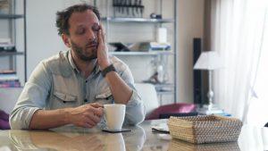 Vermoeide man drinkt koffie aan tafel