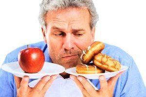 men kijkt naar gezond en ongezond voedsel en twijfelt