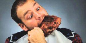 Hongerige man eet kippenpoot op