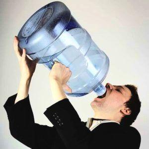 Man in pak drinkt uit grote waterkan
