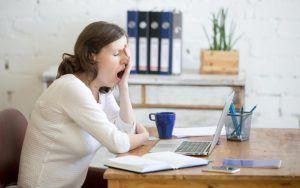 vrouw gaapt zichtbaar achter bureau