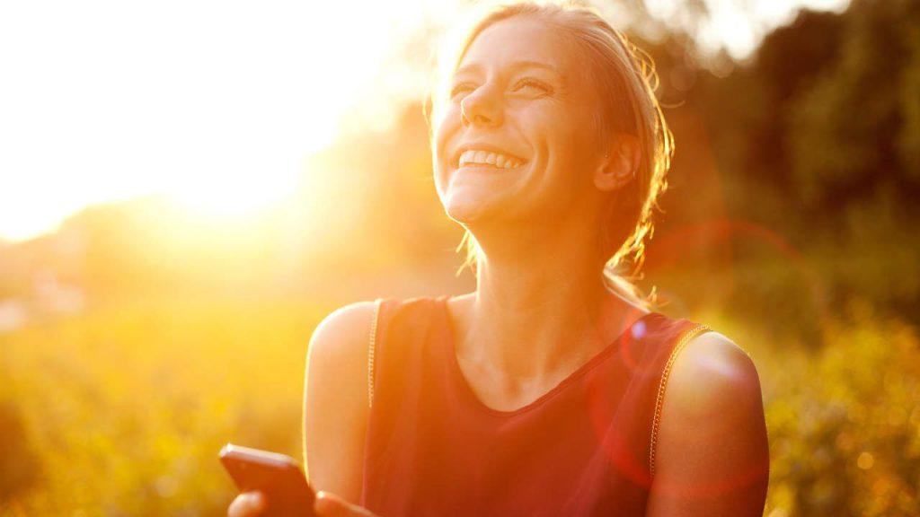 vrouw lacht buiten tijdens zonnige dag