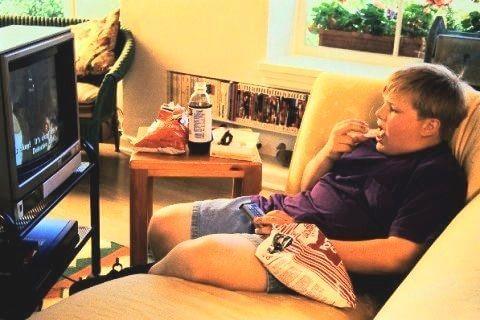 kind met overgewicht eet zak chips op bank