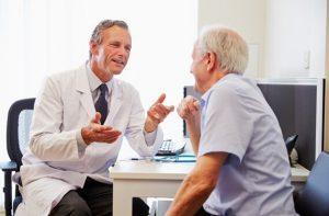 Arts praat met oude mannelijke cliënt