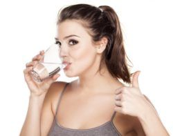 Vrouw drinkt glas water en steekt duim omhoog
