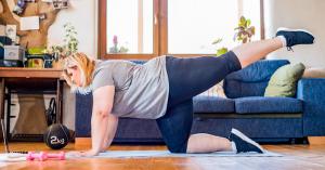 vrouw met overgewicht maakt sportbewegingen op yogamat in huiskamer