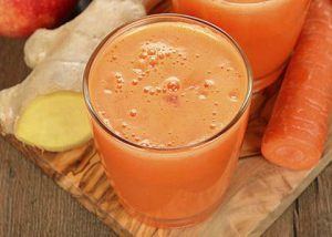 oranje smoothie in glas met wortel en gember