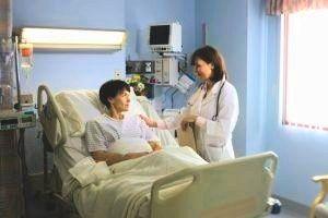 patiënt in ziekenhuisbed krijgt bezoek van arts