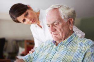 oude man kijkt neerslachtig en wordt ondersteund door zorgverlener