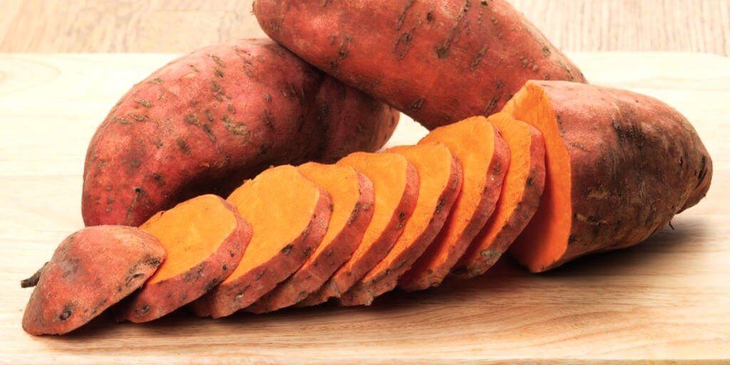 Gesneden zoete aardappel op houtenblad