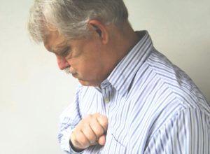 oude man klopt op borst door prikkelhoest